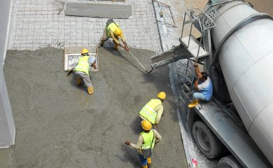 JASIN, MALAYSIA -SEPTEMBER 05, 2016: Construction workers leveling wet concrete has been poured. They also use a vibrator machine in this work.